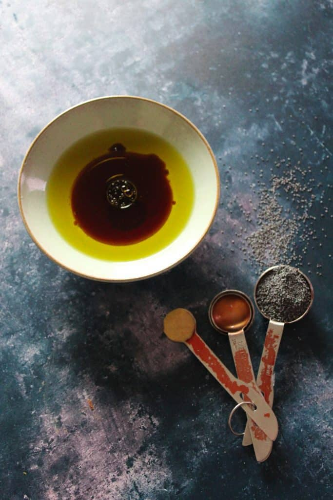 Poppyseed dressing in a small white bowl next to a measuring spoon filled with poppy seeds