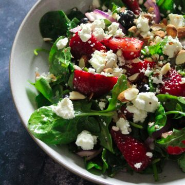Summer in a bowl! Strawberry salad bursting with blueberries, spinach, rocket and red onions, drizzled with poppyseed dressing and topped with crunchy almonds and crumbled feta. So delicious!