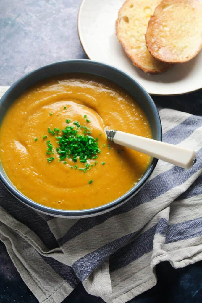 Bowl of cream of vegetable soup topped with chopped chives, next to a plate of buttered toast.