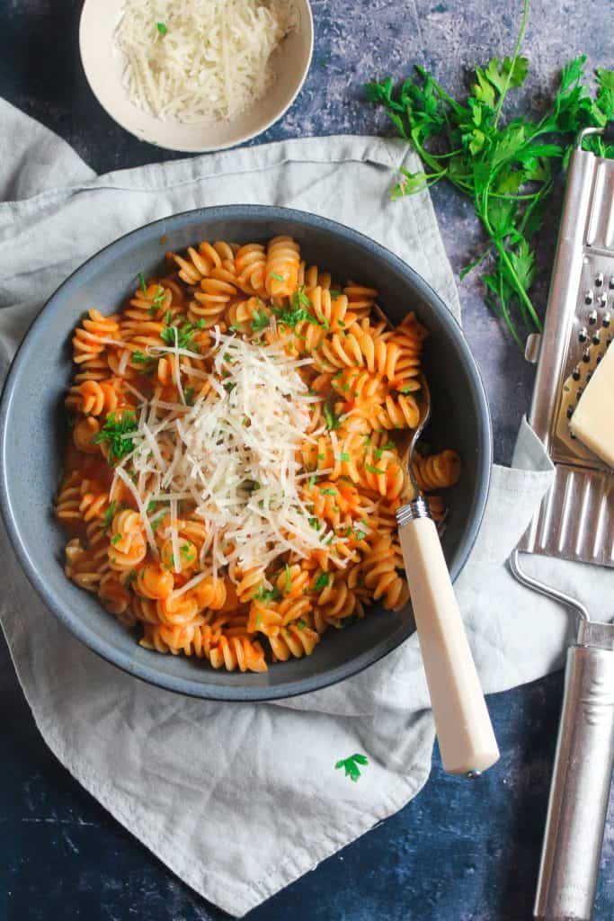 Bowl of roasted red pepper pasta with parmesan cheese