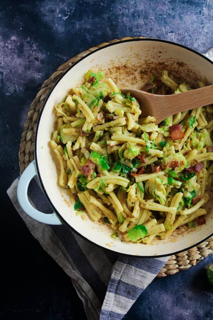 Pasta mixed with bacon, brussels sprouts and a carbonara style sauce in a blue casserole dish.