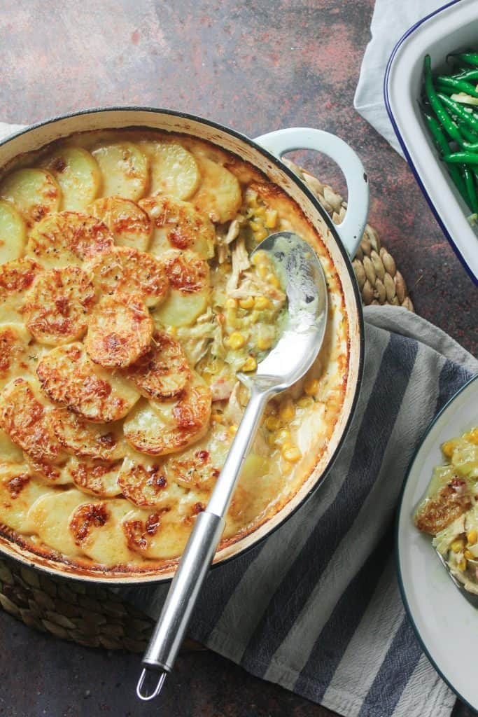 Chicken, sweetcorn and potato gratin in a shallow casserole dish with a side of steamed green beans.