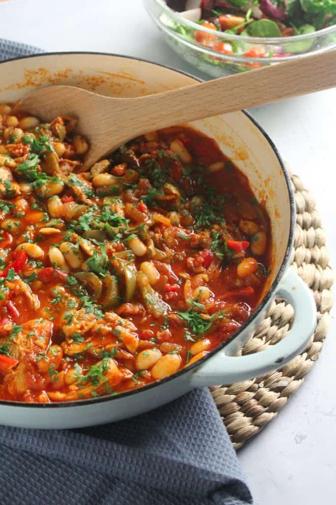 Chicken and Chorizo Stew with sliced peppers and cannellini beans in a blue cast-iron pan.