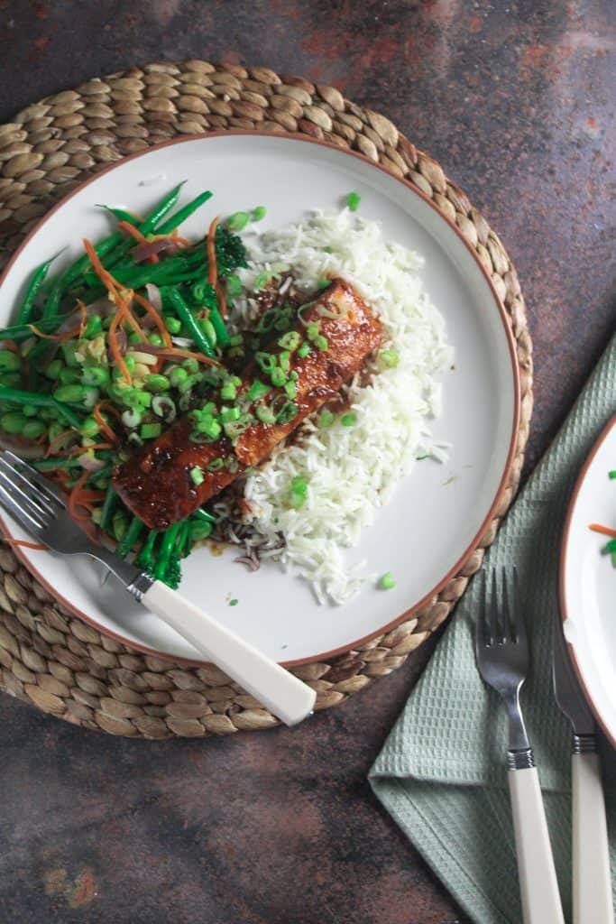 Salmon with a sweet chilli and soy glaze, on a bed on white rice next to stir fried broccoli, green beans and edamame.