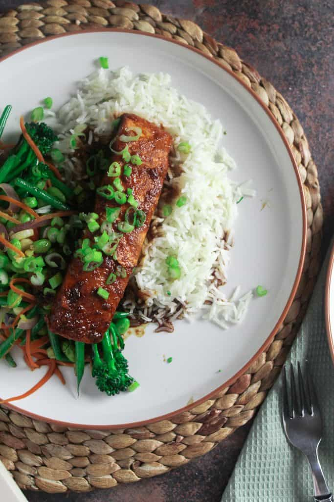 Salmon with a soy and sweet chilli sauce, on a bed of white rice with a side of stir fried green vegetables.