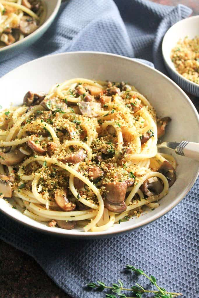 Close up of spaghetti with garlic mushrooms, topped with breadcrumbs.