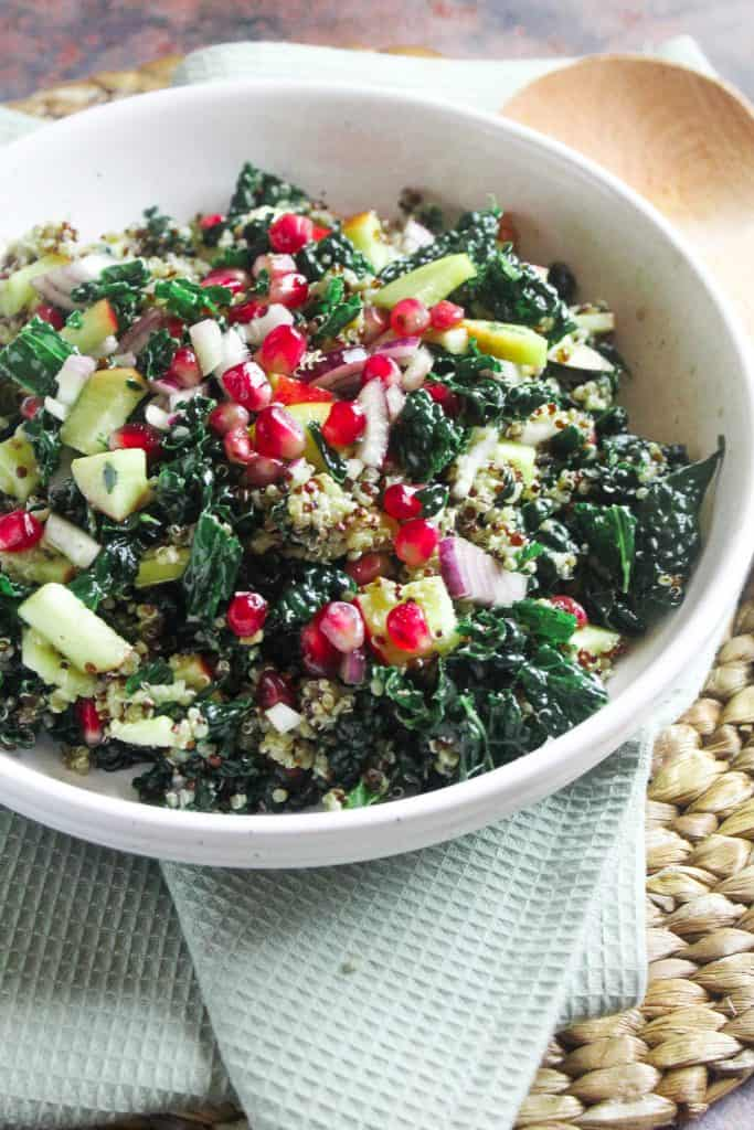Bowl of kale and pomegranate salad with apple and quinoa.