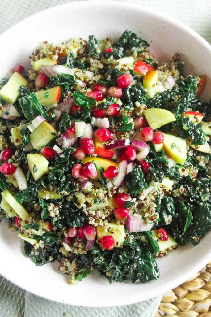 Close up of a salad made with kale, pomegranate, apple, red onion and quinoa.