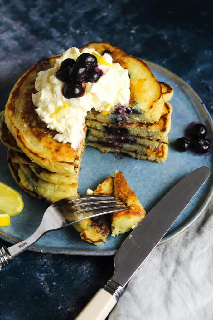 A stack of lemon blueberry pancake with a wedge cut out.