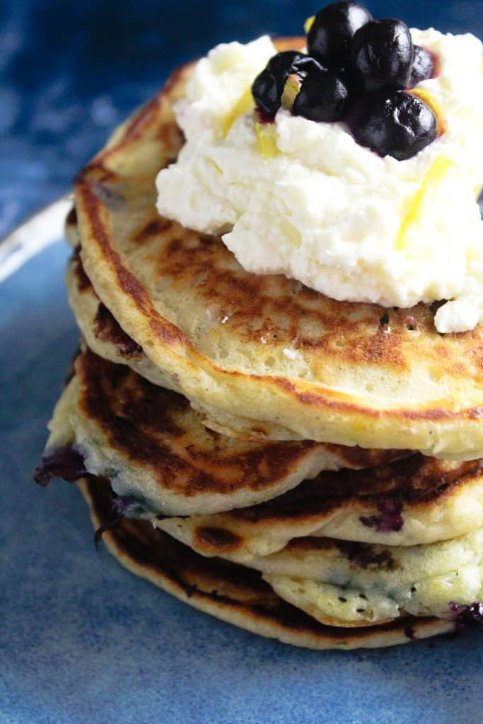 Close up of lemon blueberry pancakes topped with a dollop of lemon mascarpone cheese.
