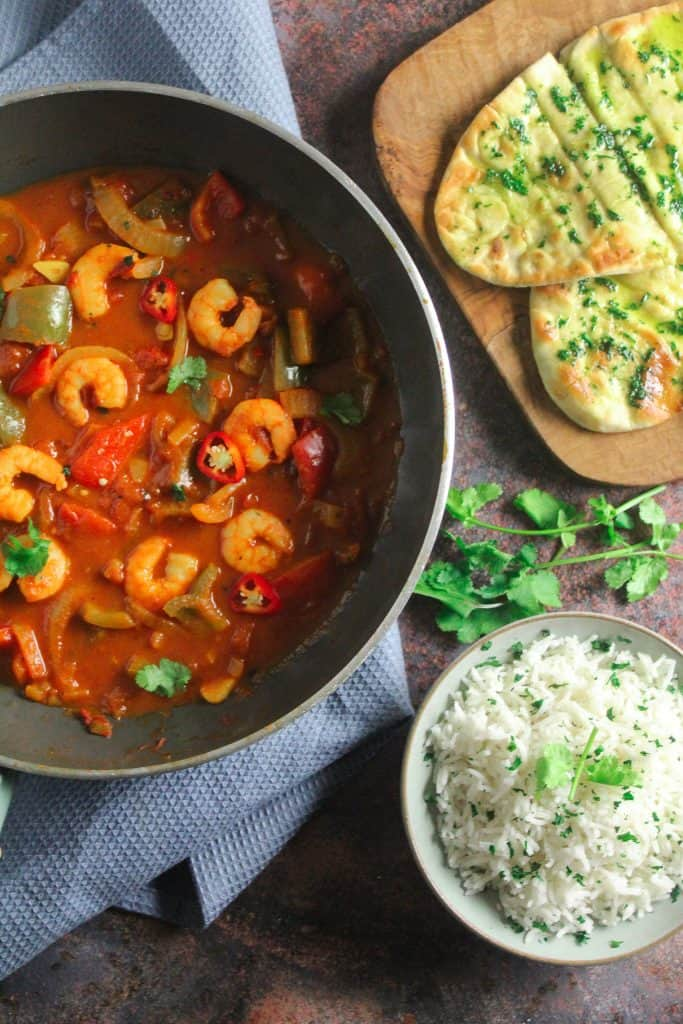 Wok containing prawn jalfrezi - prawns, peppers and sliced chilli in a tomato sauce.