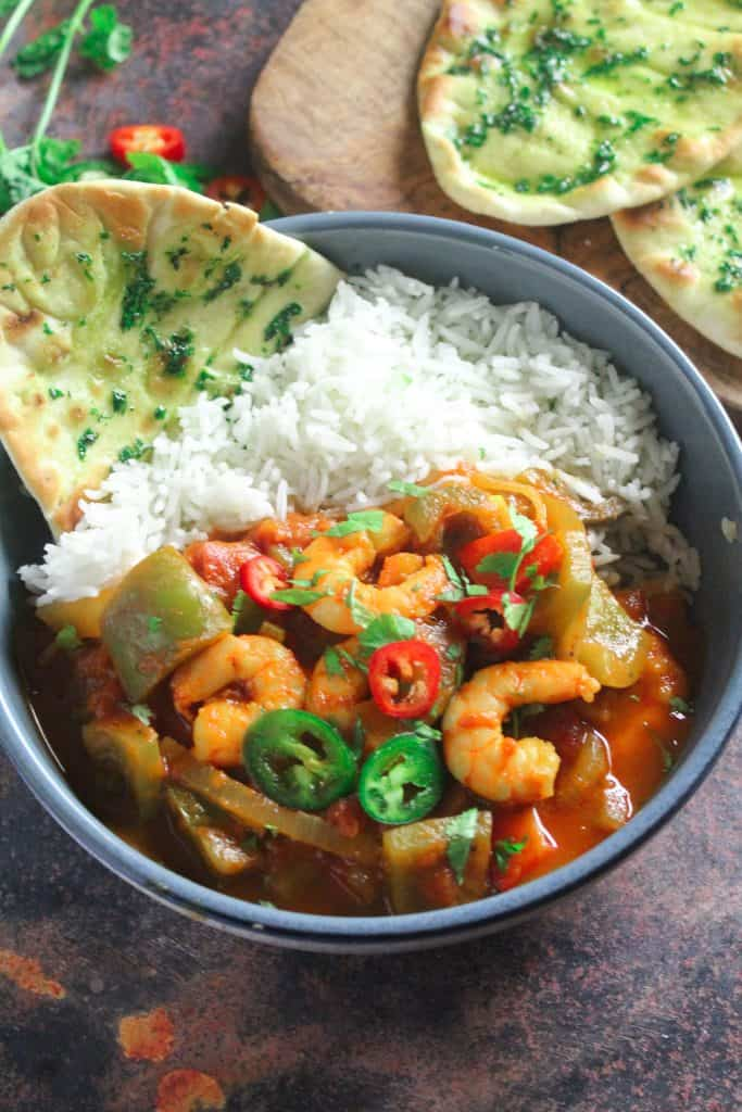 Bowl of prawns in a tomato sauce with green bell peppers. Garnished with sliced chilli and coriander. Served in a bowl with a side of rice and a flatbread.