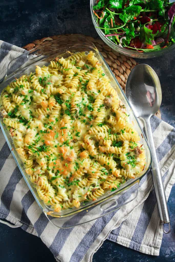 A baking dish full of fusilli pasta in a creamy tuna sauce. Topped with grilled cheddar cheese and chopped parsley.
