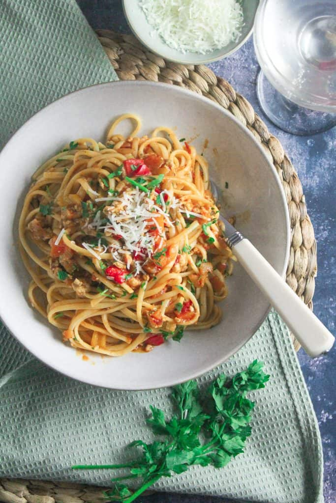 Turkey bolognese mixed with spaghetti pasta in a white bowl placed on a green mat.