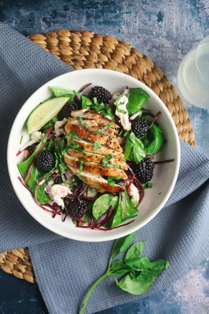 White bowl containing mixed salad leaves, juicy blackberries, crumbled cheese and torn fresh basil. Topped with a grilled, sliced chicken breast.