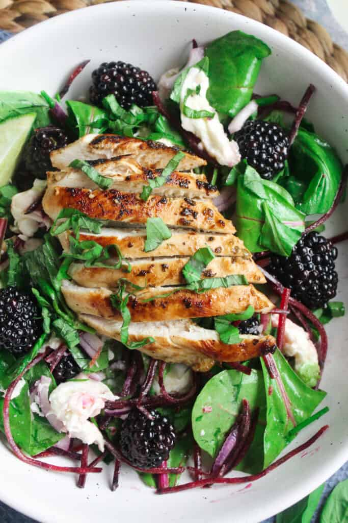 Close up of Blackberry Basil Chicken Salad - mixed leaves, blackberries, goat cheese and basil topped with a sliced grilled chicken breast.