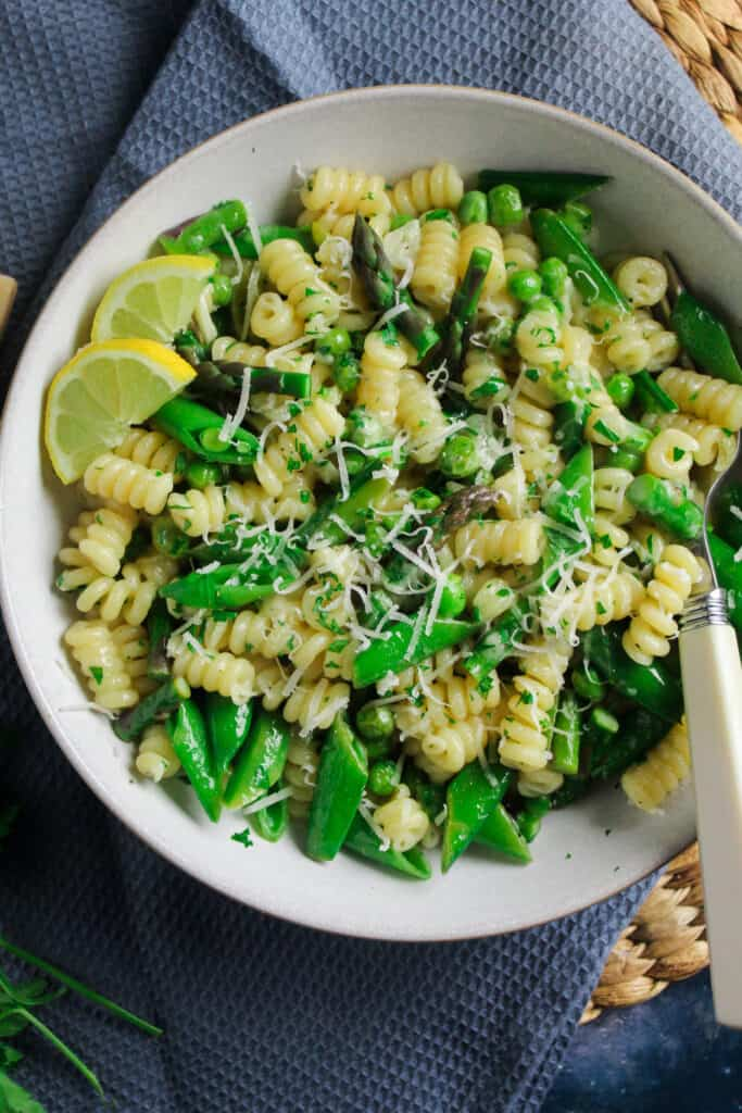 Close up of Pasta Primavera - fusilli pasta tossed with peas, sliced asparagus and snap peas. Garnished with lemon slices, chopped parsley and grated parmesan cheese.