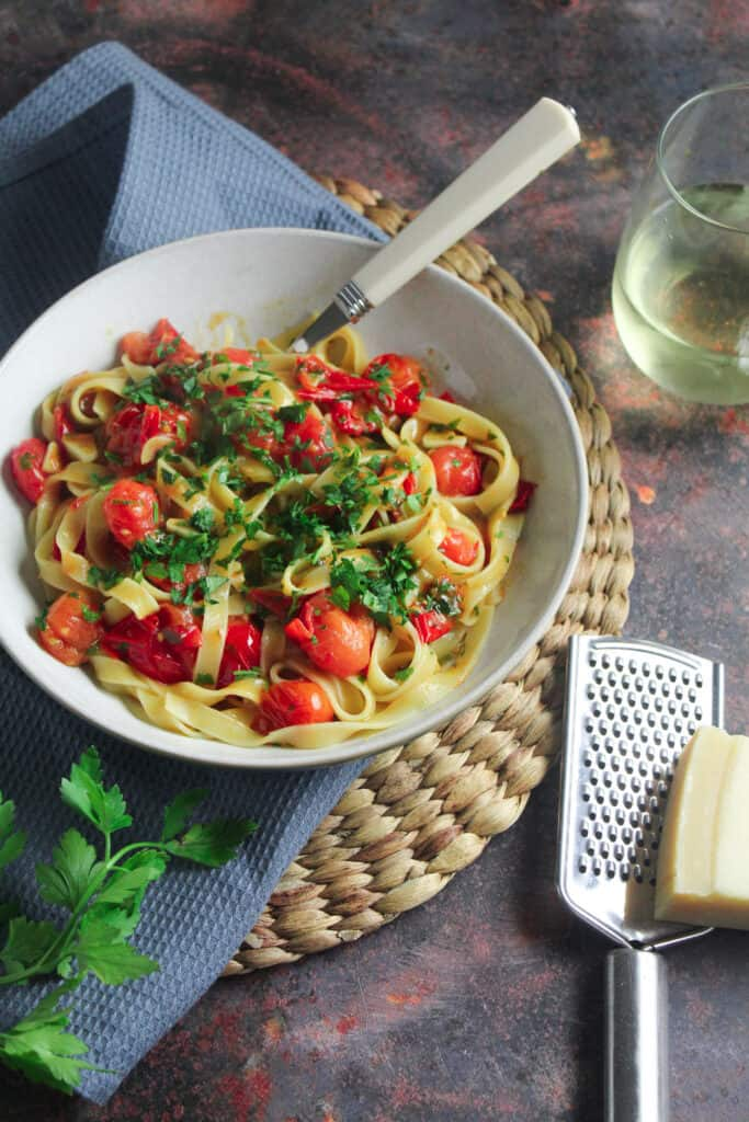 A bowl of tagliatelle pasta with blistered cherry tomatoes mixed through and garnished with fresh chopped basil.