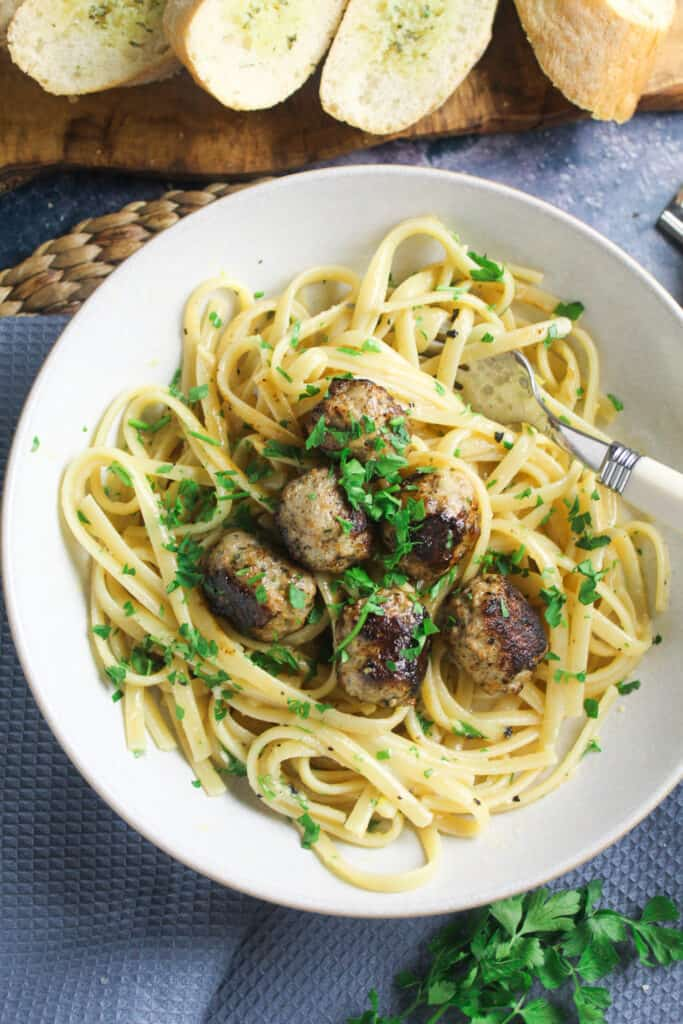 Close up of a bowl of Sausage Carbonara sprinkled with parsley.