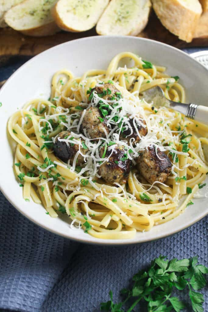 Sausage Carbonara - spaghetti in carbonara sauce with lemon and parsley. Topped with sausage meatballs and garnished with fresh parsley and grated parmesan.