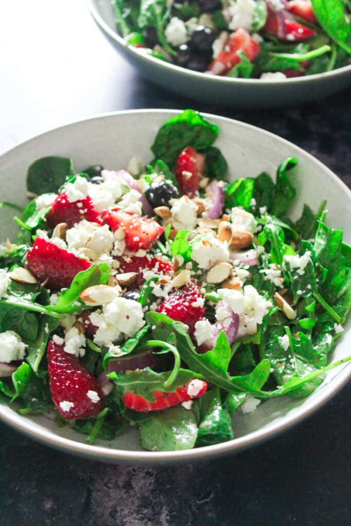 Close up of Strawberry Spinach Salad topped with crumbled feta and chopped almonds.