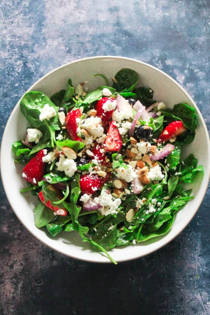 Bowl of Strawberry Spinach Salad - strawberries, spinach, rocket, blueberries and red onion topped with feta cheese and chopped almonds.