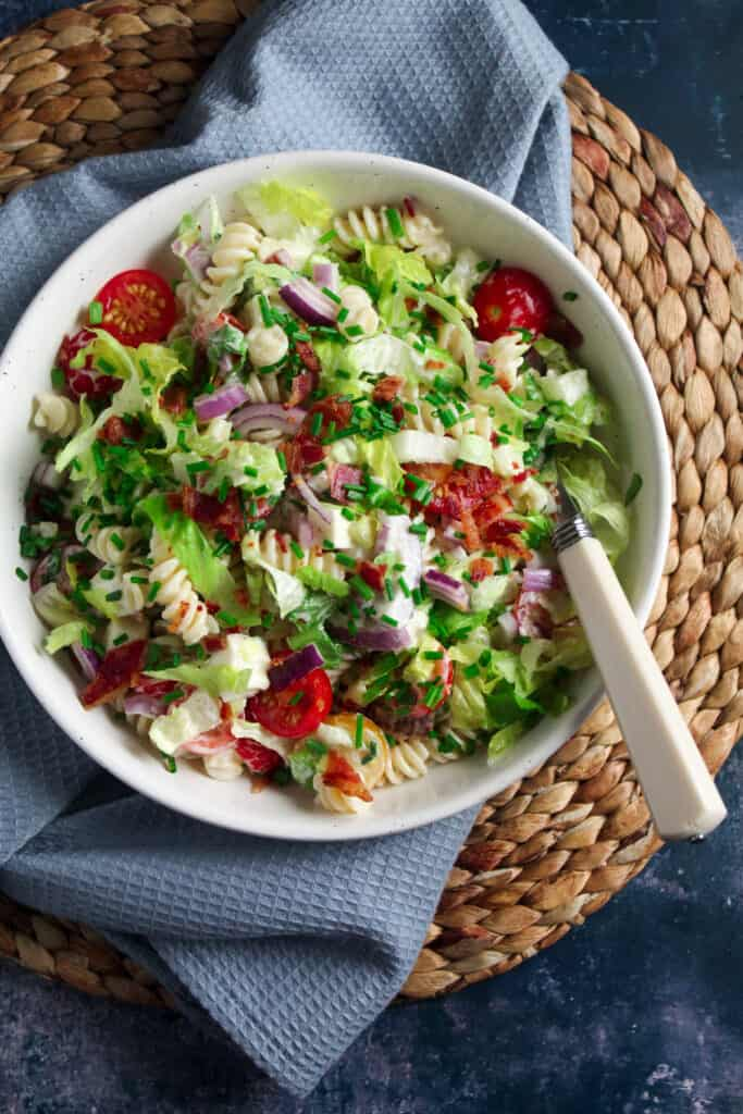 White bowl on a woven mat containing BLT Pasta Salad - fusilli pasta, crispy bacon pieces, shredded lettuce, cherry tomatoes, sliced red onion and mozzarella topped with fresh cut chives.