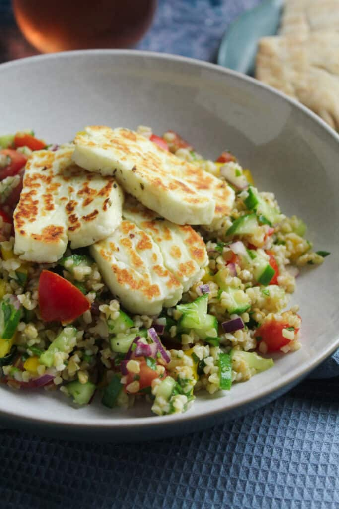 Close up of a bowl of bulgur wheat salad topped with slices of thick cut fried halloumi cheese.
