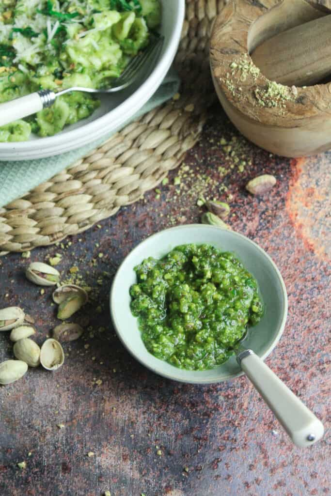 Close up of pistachio pesto in a small green bowl. There are pistachios and pistachio shells scattered around it.