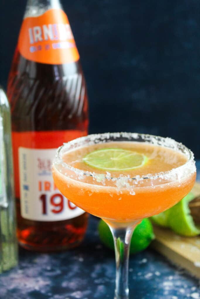 Irn Bru Margarita - a margarita glass with a salted rim filled with bright orange liquid.