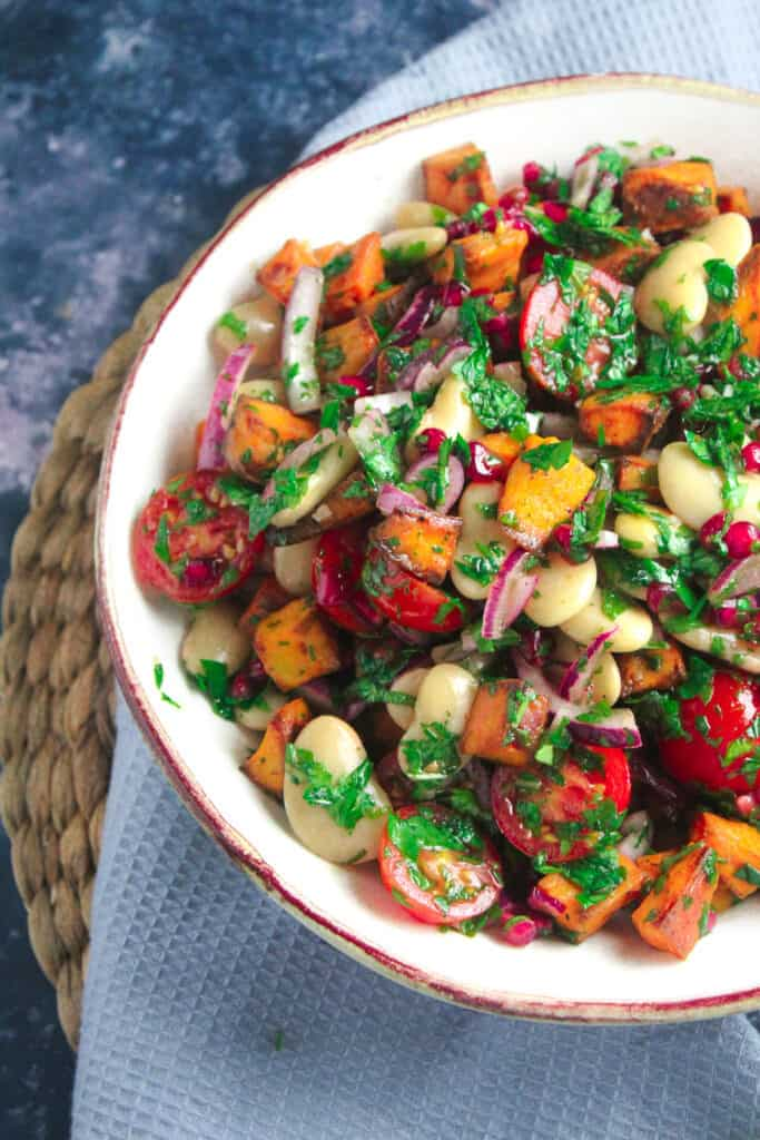 White bowl containing chunks of roast sweet potato, halved cherry tomatoes, pomegranate seeds, sliced red onion, butter beans and fresh herbs.