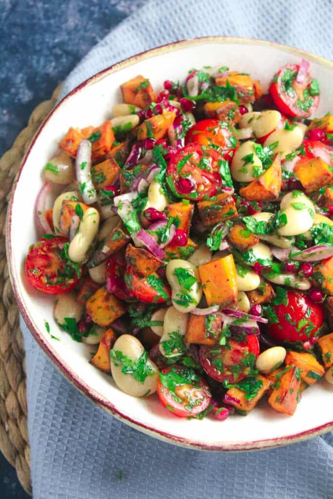 Bowl of roast sweet potato salad with pomegranate and tomato.
