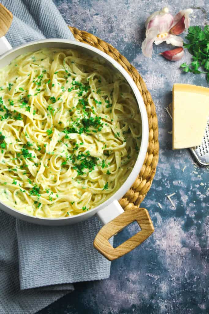 Large pot containing fettuccine pasta in a creamy white sauce. The pasta is garnished with chopped parsley.